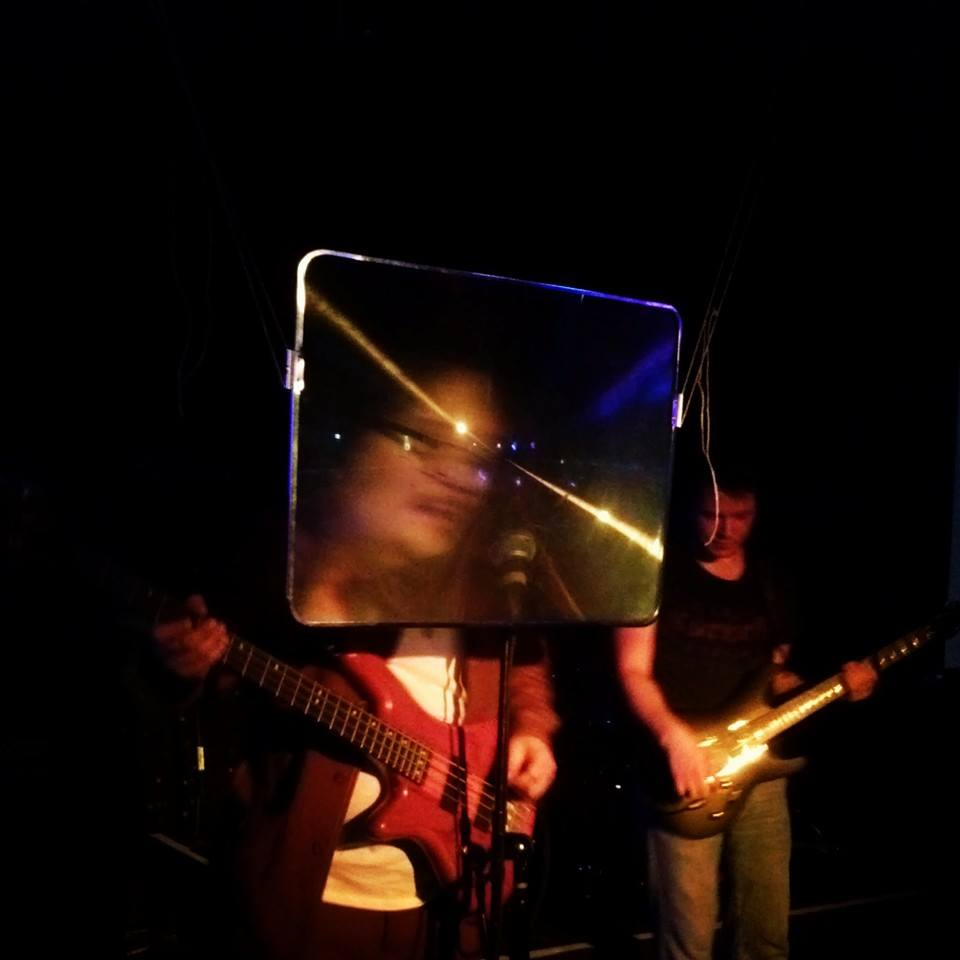 Dead Birds Adore Us Album Release show photo. The Bass player's head is enlarged using a projector magnifying screen.